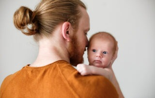 A baby looking over the shoulder of the man holding him.