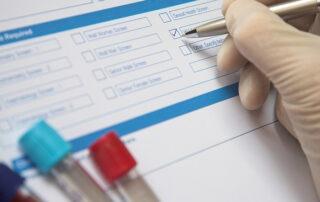 Doctor Completing A Blood Test Form For PSA
